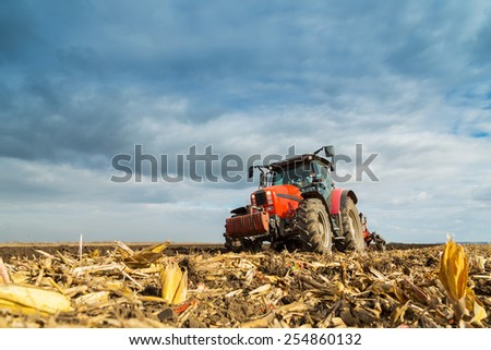 Farmer plowing with red tractor - stock photo