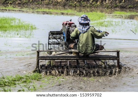 farmer ride rice tractor for preparing the ground for rice plantation. - stock photo