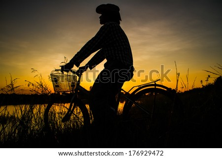 Farmer riding bicycle beside the pond in the evening. - stock photo