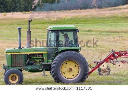 Farmer's daughter plowing field. - stock photo