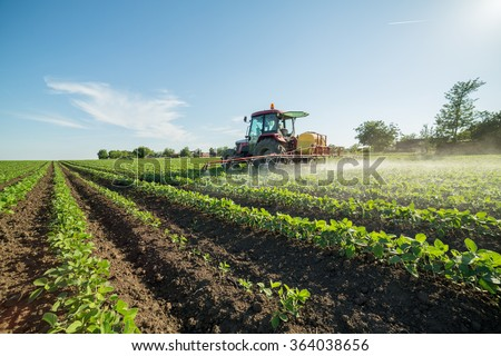 Farmer spraying soybean field with pesticides and herbicides - stock photo