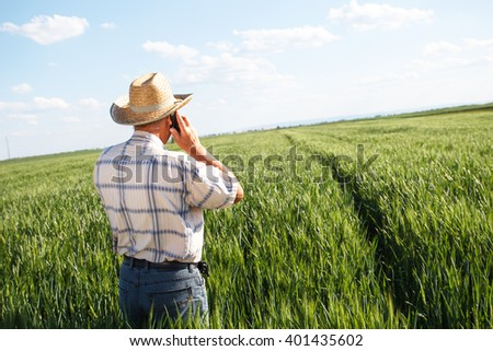 Farmer standing in a wheat field and talking on phone - stock photo