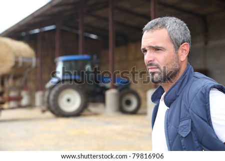 Farmer standing in front of a barn containing a tractor - stock photo