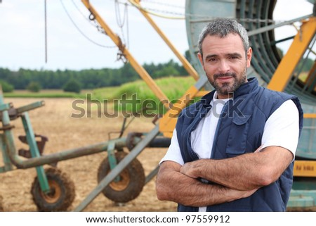 Farmer stood by irrigation system - stock photo
