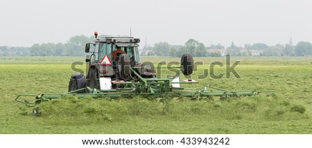 Farmer uses tractor to spread hay on the field where it will dry - stock photo