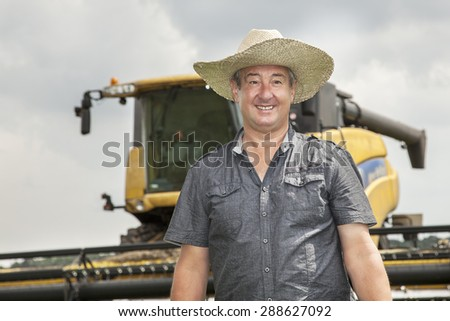 Farmer with combine harvester - stock photo