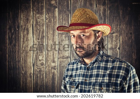 Farmer with cowboy straw hat in front of wooden byre wall - stock photo