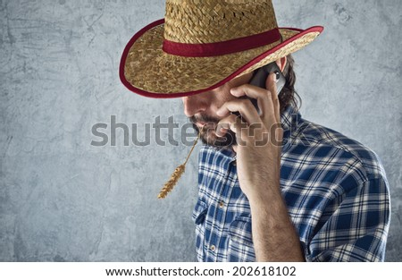 Farmer with cowboy straw hat talking on mobile phone - stock photo