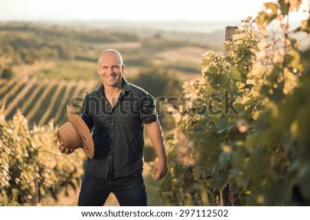 Farmer with hat standing in his vineyard - stock photo