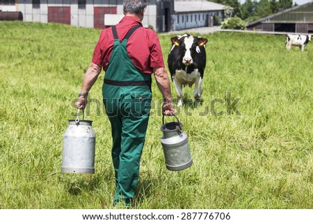 farmer with milk churns at his cows