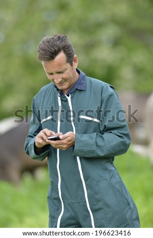 Farmer with overall sending message with smartphone - stock photo