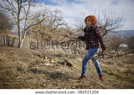 Farmer woman cleaning the branches in an orchard after pruning