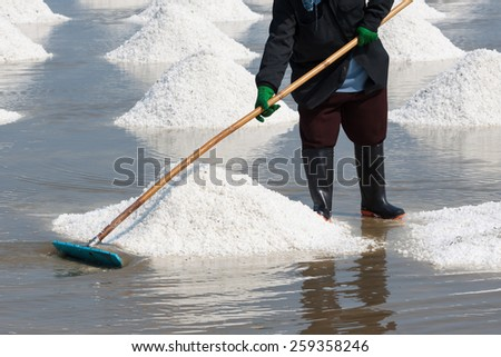 Farmer working at Salt pile in Thailand, Salt Pan. - stock photo