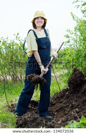 farmer works with manure at farm - stock photo