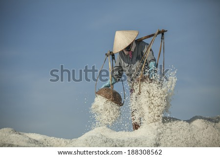 Farmers carrying the salt on the baskets in Nha Trang, Vietnam - stock photo
