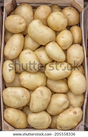 Farmers market potatoes in a wooden crate background. At the farmers market local growers come and sell their freshly picked crops at reasonable prices.