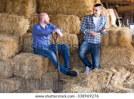 Farmers sitting on a stack of straw and talking to each other while taking a break in their work day at a farm