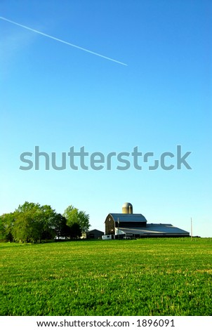 Farmhouse and barn among green fields, vertical