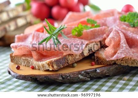 Farmhouse bread with delicious salami - stock photo
