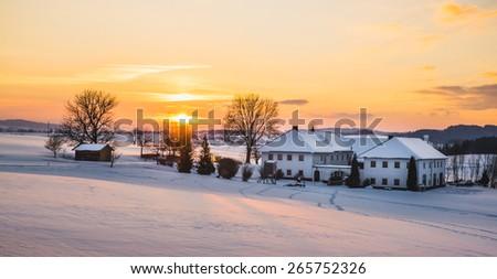 Farmhouse in a winter landscape at sunrise taken in upper austria - stock photo