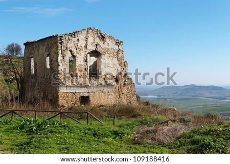 Farmhouse ruin among rural landscape - stock photo