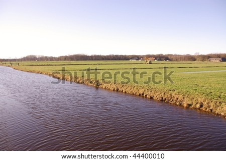 Farmhouses with meadows and a canal - stock photo