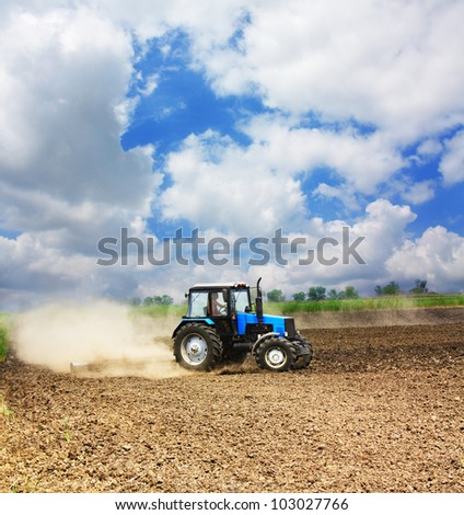 Farming blue tractor in a field, agricultural scene in summer - stock photo