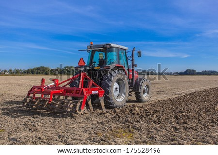 Farming in the Netherlands, Tractor with Plough in a Field under Blue Sky - stock photo