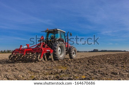 Farming in the Netherlands, Tractor with Plough, Plowing in a Field under Blue Sky - stock photo