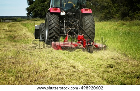 Farming: Large red tractor moving green farmers pasture, motion close up