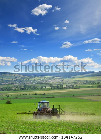 Farming tractor plowing and spraying on field - stock photo