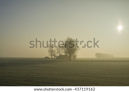 Farmland and windturbines on the horizon on an early, foggy morning  - stock photo