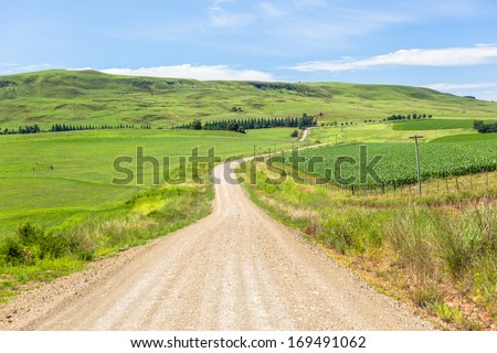 Farmland Dirt Road Mountains  Mountain countryside dirt road travels over the rural farming landscape into the distance