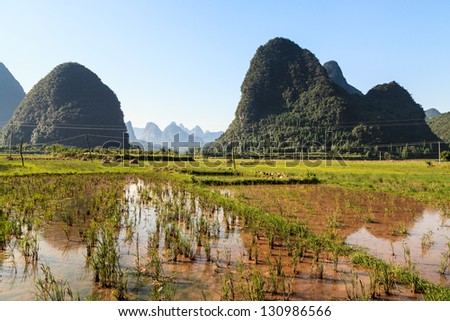 Farmland in a valley with limestone rocks around in morning sun - stock photo