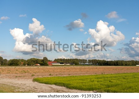 Farmland in the Netherlands with a typical Dutch cloudscape - stock photo