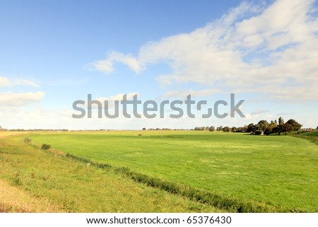 Farmland with blue cloudy sky, the Netherlands - stock photo