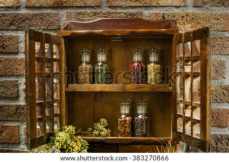 Farms vintage Spice Rack or Storage Cabinet: Wall Mount - Display Shelf, Six Glass Bottleson rural background village life - stock photo