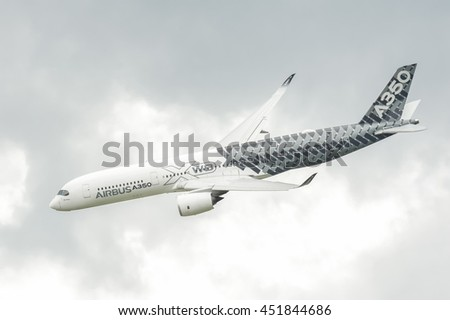 FARNBOROUGH, UK - JULY 13: Airbus A350-941 circling in cloudy skies above before landing at Farnborough, Hampshire, UK on July 13, 2016 - stock photo