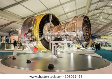 FARNBOROUGH, UK - JULY 12: Exhibition stands displaying large jet engines and other components used in the aviation industry at the Farnborough International Airshow, UK on July 12, 2012