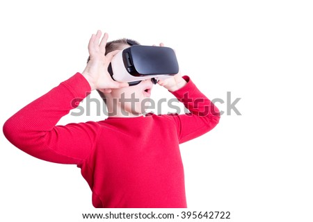 Fascinated male child in red long sleeve shirt holding and looking through virtual reality glasses over white background - stock photo