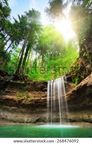 Fascinating wide-angle landscape shot of a paradise with waterfalls on multi-layered cliffs, fresh green forest, blue sky and the sun shining bright - stock photo