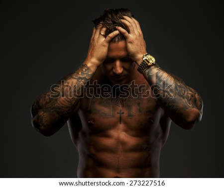 Fashinable muscular man with tattooes on grey background - stock photo