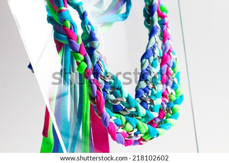 Fashion accessories: very colourful necklaces made by weaving lycra ribbons and metal chains together. - stock photo