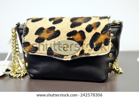 Fashion and glamorous leopard handbag with gold chain on display at a fashion store - stock photo