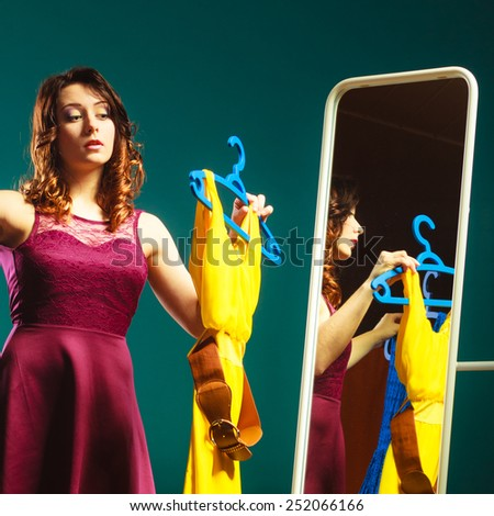 Fashion and shopping. Woman preparing to party, trying dress choosing clothing. Attractive young woman shopper looking in mirror, standing in clothes store. - stock photo