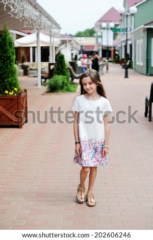 Fashion and stylish brunette kid girl walking in the center of busy street in outlet shopping village during summer sales period  - stock photo