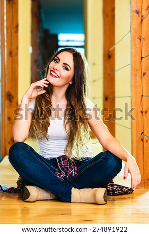 Fashion and young people concept - Full length teen girl long curly hair in denim trousers casual style relaxing at home, sitting on floor - stock photo