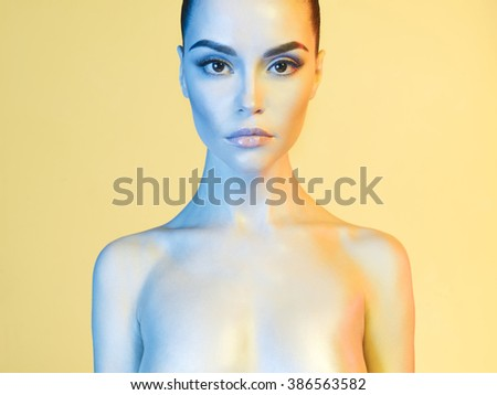 Fashion art photo of elegant nude model in the light colored spotlights - stock photo