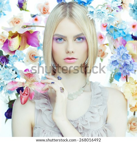 Fashion art portrait of beautiful lady in delicate flowers around - stock photo