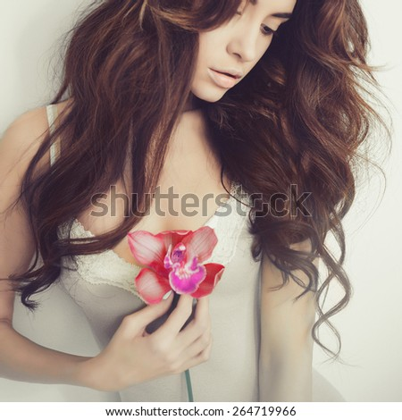 Fashion art portrait of beautiful lady with delicate flowers